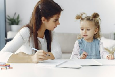A kid is reading with her mother